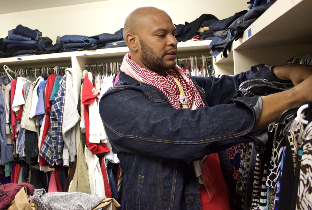 "Jermaine Harmon picks out clothes from the donations to imitate the shopping experience offered to members. Harmon says,""It's just kind of like, 'where's the sales rack?'"" (Photo: Chantal de la Rionda 